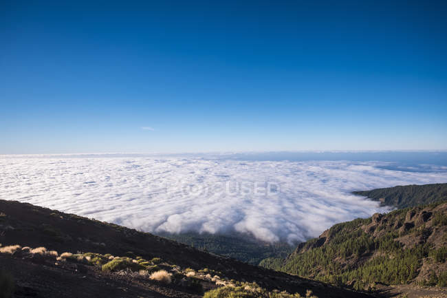 Spain, Tenerife, Teide National Park, mountains in clouds with blue sky — Stock Photo