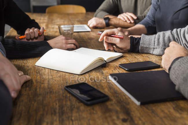 Коллеги работают над проектом по деревянному столу — стоковое фото