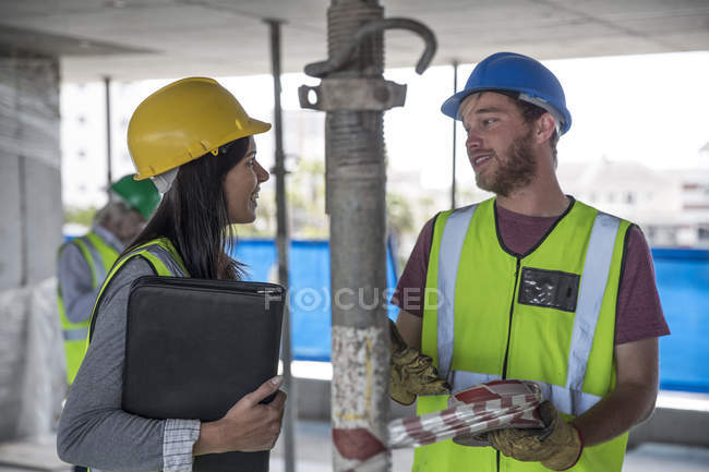 Engineer inspecting construction site, talking to workers — Stock Photo