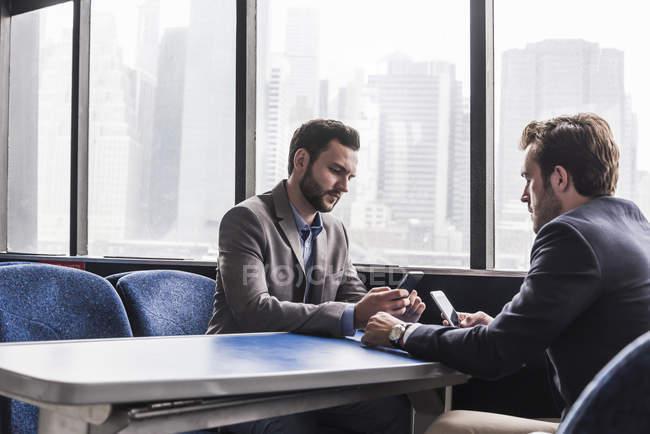 Dois homens de negócios usando telefones celulares no convés de passageiros de um ferry — Fotografia de Stock