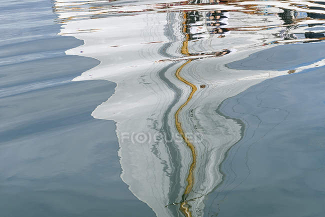 Sailing boat reflecting in water of a lake — Stock Photo
