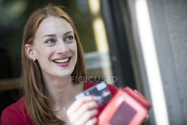 Portrait of smiling woman with purse and credit card — Stock Photo