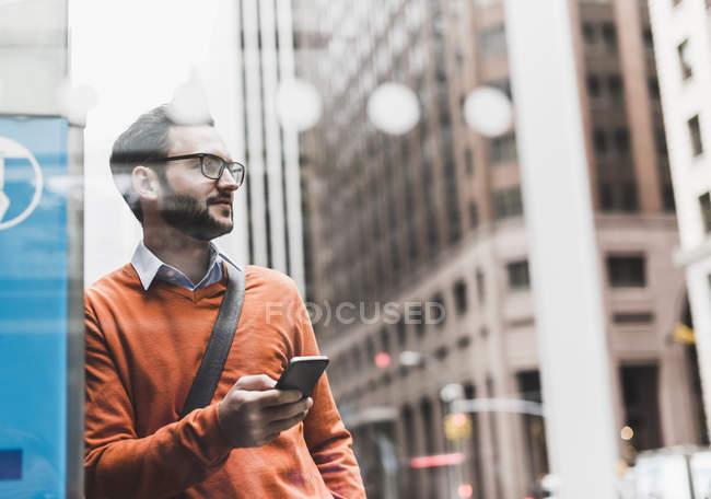 Homme d'affaires appuyé sur un smartphone ATM Holding, New York, États-Unis — Photo de stock