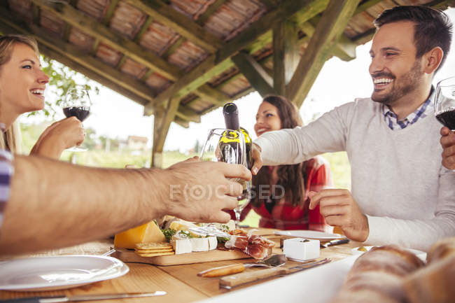 Friends socializing at outdoor table with red wine and snacks — Stock Photo
