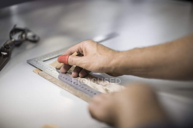 Tailor measuring cloth in designer factory — Stock Photo