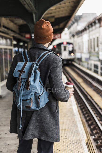 Young man waiting at metro station platform and holding disposable cup — Stock Photo