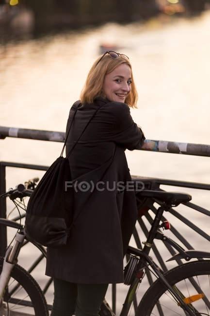Rückansicht einer jungen attraktiven blonden Frau, die mit Fahrrad neben Zaun steht — Stockfoto