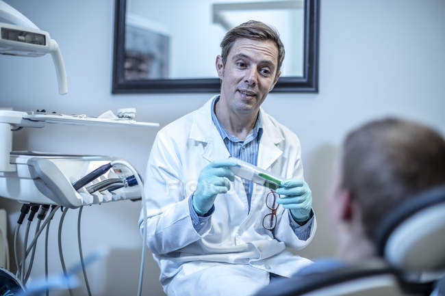 Dentist holding toothbrush talking to boy in dental surgery — Stock Photo