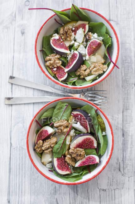 Дві миски салат з Мангольд, сир фета, інжир, груші та волоські горіхи на сірий деревини з вилами — стокове фото