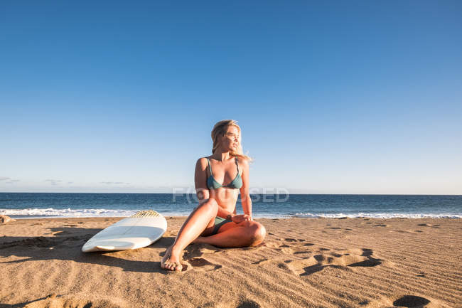 Испания, Тенерифе, молодой блондин серфер, сидя на пляже — стоковое фото