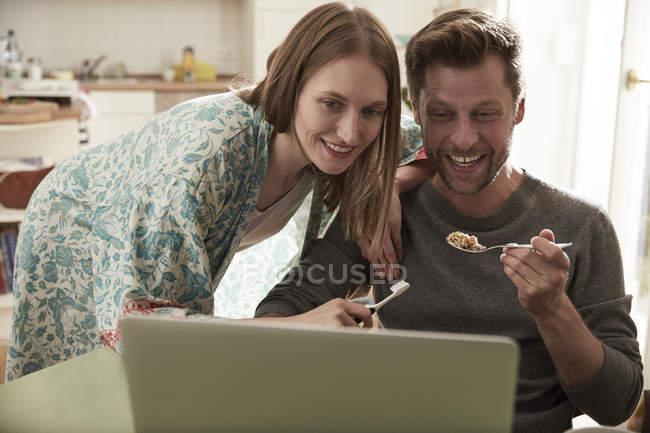 Pareja feliz mirando juntos el portátil, mujer con cepillo de dientes, hombre con cuchara de granola - foto de stock