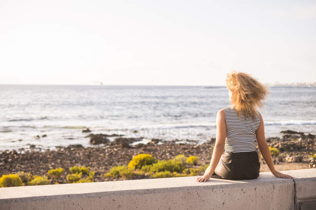 Woman sitting on a wall and looking at the sea — Stock Photo