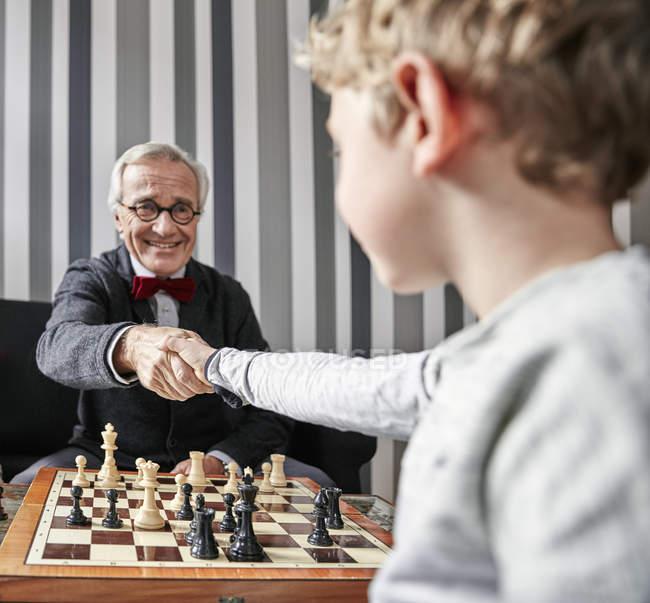 Дідусь і онук, потискує руку над шахівниця — стокове фото