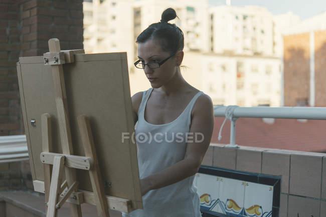 Молодая женщина рисует на террасе своего пентхауса — стоковое фото
