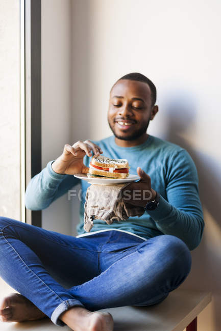 Young man eating a club sandwich — Stock Photo