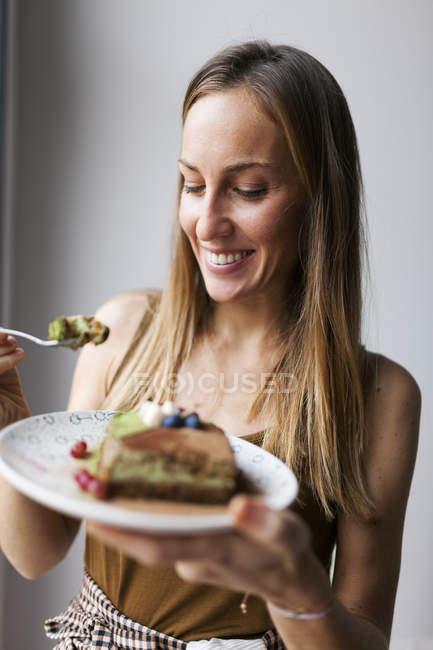 Woman eating vegan matcha cake — Stock Photo