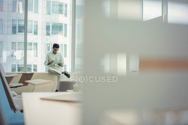 Бізнесмен, сидячи на підвіконні і використовуючи цифровий планшетний — стокове фото