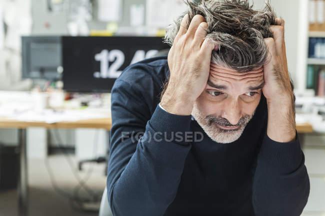 Maduro homem sentado no escritório com cabeça no mãos — Fotografia de Stock