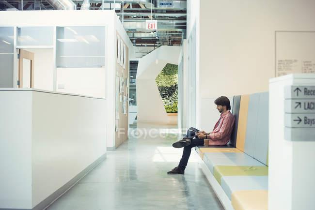 Молодий підприємець сидить у фойє, використовуючи цифровий планшетний — стокове фото
