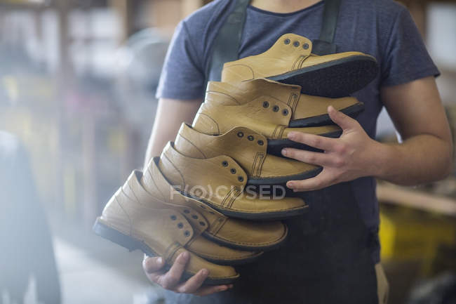 Shoemaker holding stack of shoes — Stock Photo