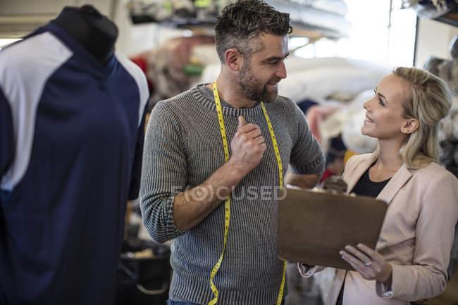 Medida con cinta métrica hablar con mujer con portapapeles en taller - foto de stock