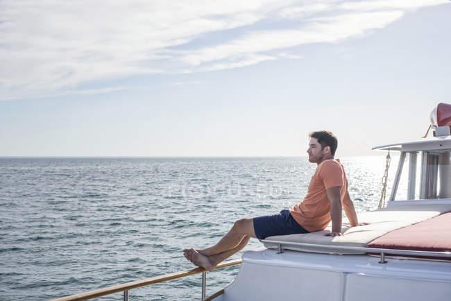 Молодой человек, сидящий на лодке и отворачивающийся — стоковое фото