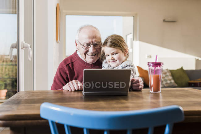 Grandfather and granddaughter using laptop together at desk — Stock Photo