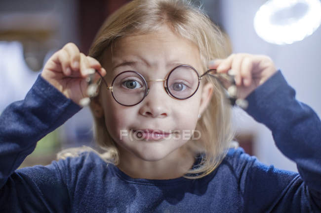 Little girl looking through spectacles, closeup — Stock Photo