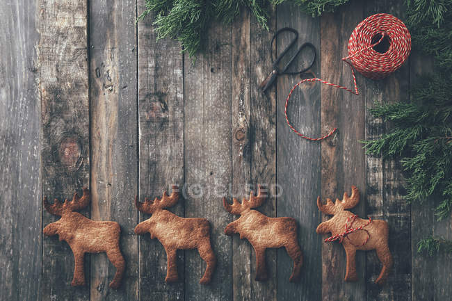 Row of four Elk-shaped Christmas cookies on dark wood — Stock Photo