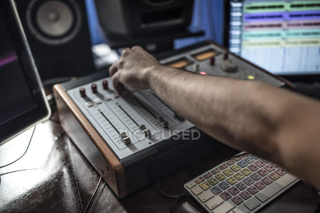 Close-up of audio engineer operating mixer in recording studio — Stock Photo