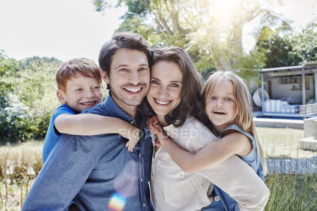 Retrato de familia feliz abrazando en jardín - foto de stock