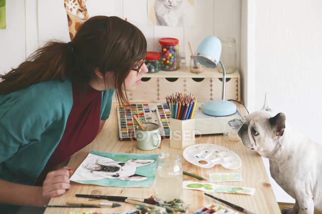 Artist watching French bulldog in her studio — Stock Photo