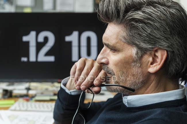 Uomo maturo tenendo gli occhiali, pensando a soluzioni — Foto stock