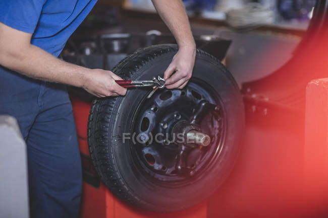 Cropped image of Mechanic checking tire — Stock Photo
