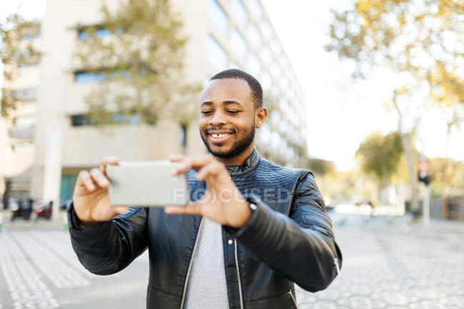 Smiling young man taking selfie with smartphone — Stock Photo