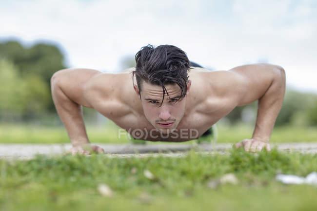Joven muscular hombre haciendo flexiones al aire libre - foto de stock
