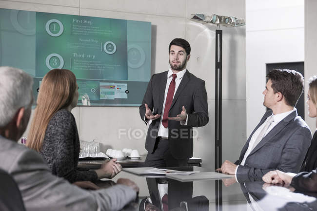Businessman holding presentation in front of team — Stock Photo