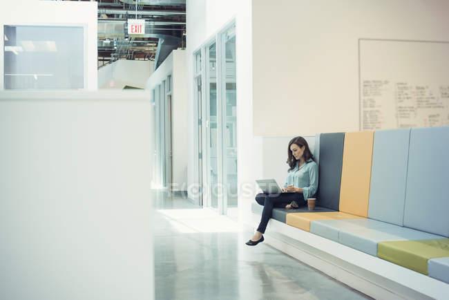 Молодий бізнес-леді сидить на лавці, використовуючи ноутбук — стокове фото
