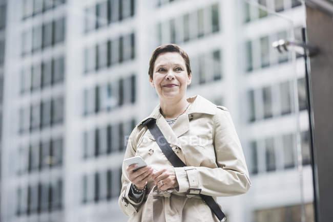 Mulher sorridente em Manhattan com telefone celular, Nova York, EUA — Fotografia de Stock