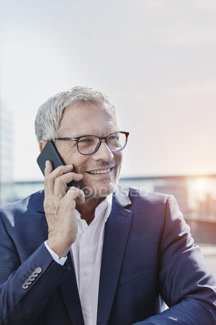 Smiling businessman on cell phone outdoors — Stock Photo