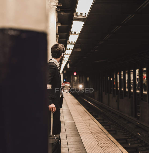 Young businessman waiting at metro station platform — Stock Photo