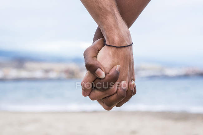 Close-up of two hands connected on the beach — Stock Photo