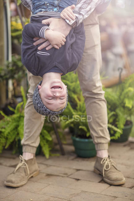 Father holding his son upside down — Stock Photo