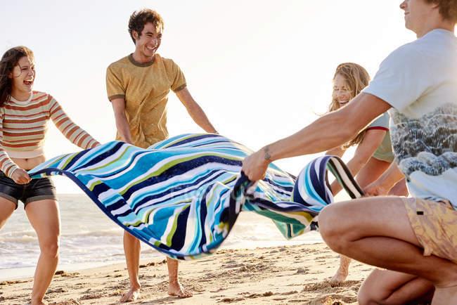 Heureux amis étaler serviette sur la plage — Photo de stock