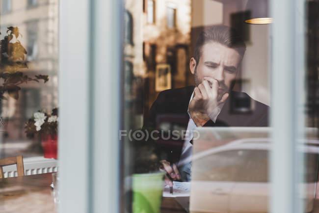 Junger Geschäftsmann arbeitet in einem Café mit Laptop hinter Fensterscheibe — Stockfoto