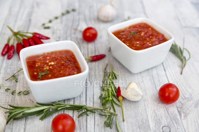 Two bowls of homemade tomato sauce and ingredients on wood — Stock Photo