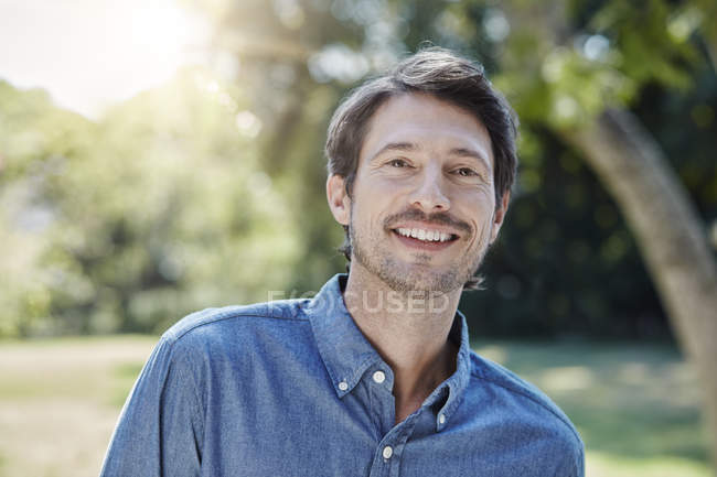 Portrait of caucasian smiling man in park — Stock Photo