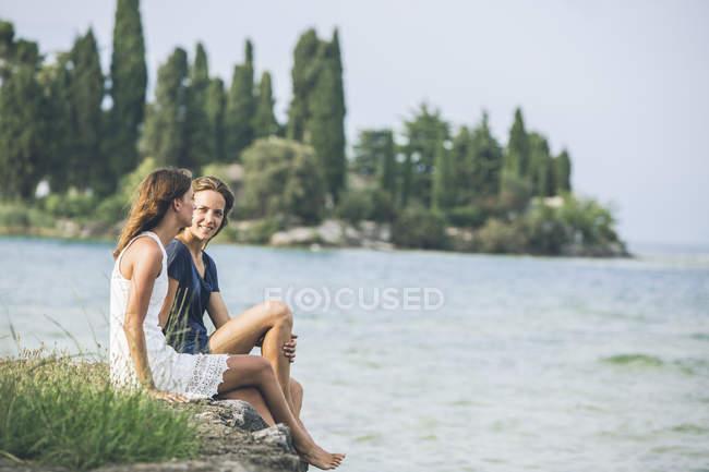 Italy, Lake Garda, two young women sitting at lakeshore — Stock Photo