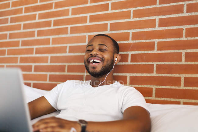Сміючись молода людина з навушники ліжко, використовуючи ноутбук — стокове фото