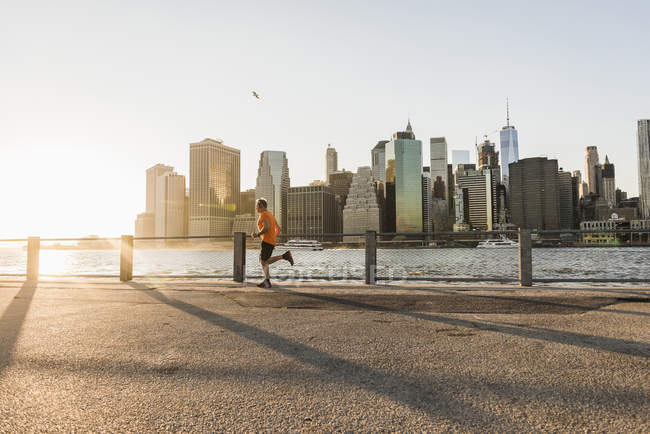 США, Бруклін, людина, біг підтюпцем перед Манхеттен увечері — стокове фото